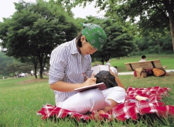 girl sitting on picnic blanket, writing