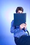 Girl hiding behind blue book.